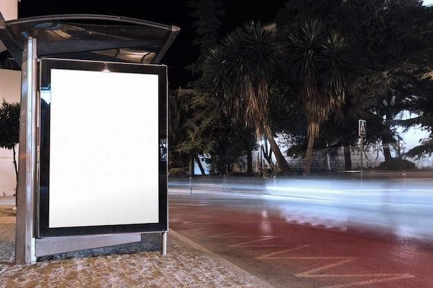 Tabellone per le affissioni in bianco sul riparo della fermata dell'autobus alla notte