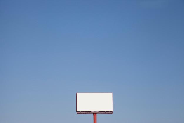 Tabellone per le affissioni tesaurico in bianco contro cielo blu