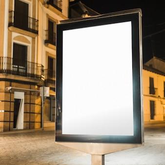 Tabellone per le affissioni verticale illuminato in bianco alla notte