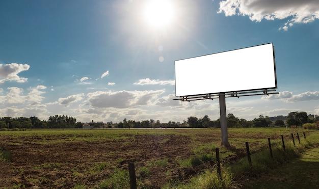Tabellone per le affissioni vuoto davanti al bel cielo nuvoloso in una posizione rurale