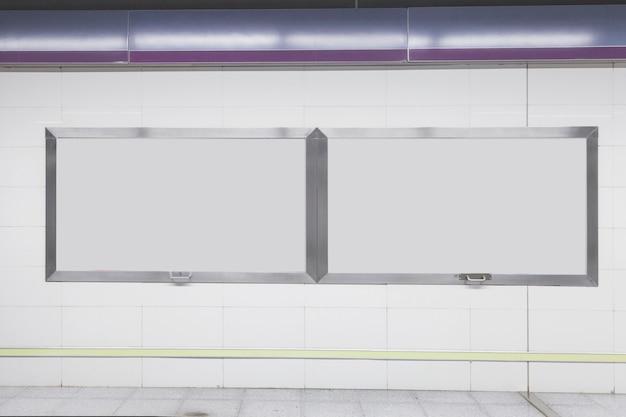 Tabellone per le affissioni vuoto in bianco sulla parete bianca