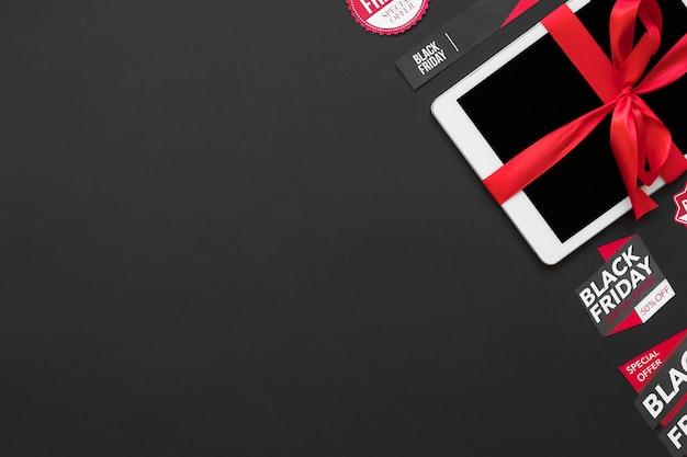 Tablet bianco con nastro rosso tra tag di vendita