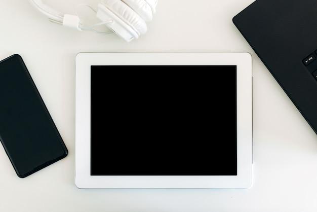 Tablet bianco e uno smartphone sulla scrivania