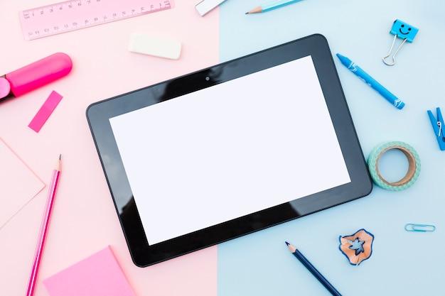 Tablet con elementi decorativi intorno su sfondo colorato