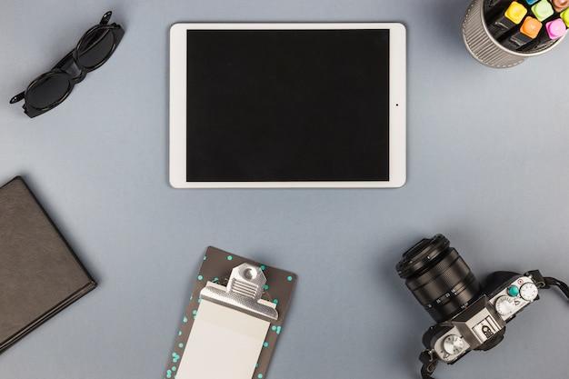 Tablet con notebook e fotocamera sul tavolo
