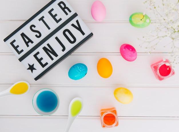 Tablet con pasqua godono titolo vicino a uova tra ramoscello di fiori e lattine con liquido colorante