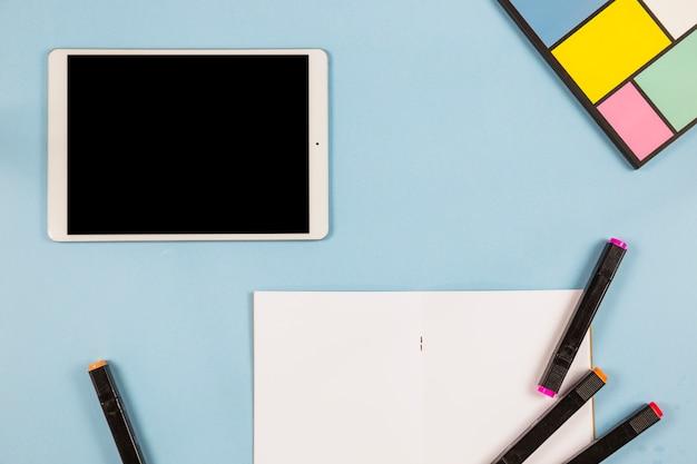 Tablet con pennarelli e carta sul tavolo