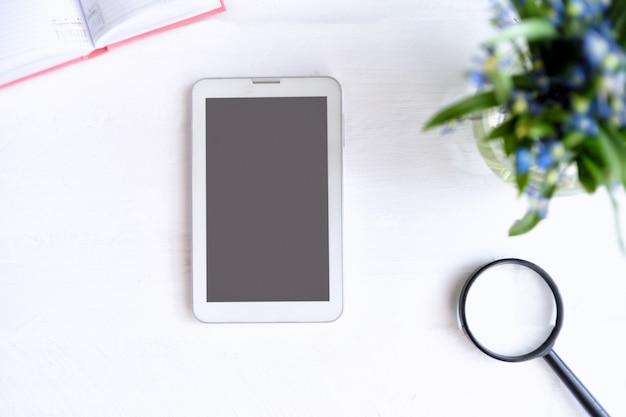 Tablet con schermo nero vuoto. taccuino, lente d'ingrandimento e fiori sul tavolo