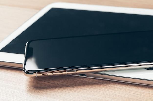 Tablet digitale e telefono cellulare. apparecchi elettronici sulla tavola di legno, fine su.