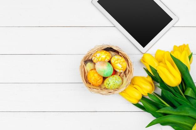 Tablet, fiori di tulipano colorati e uovo di pasqua