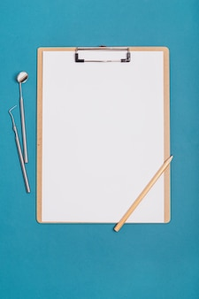 Tablet per record su uno sfondo blu con strumenti dentali