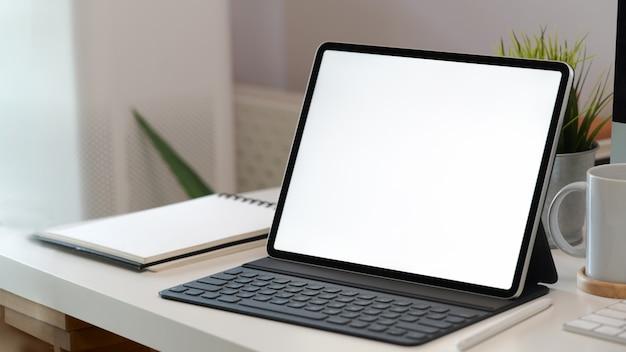 Tablet schermo bianco con tastiera intelligente sulla scrivania dell'area di lavoro