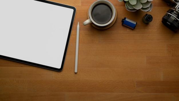 Tablet sulla scrivania in legno con copia spazio, tazza di caffè, macchina fotografica e decorazione