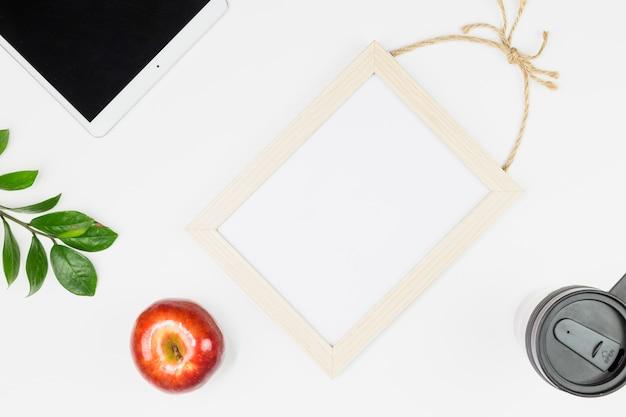 Tablet vicino a mela, pianta ramoscello, tazza e cornice per foto