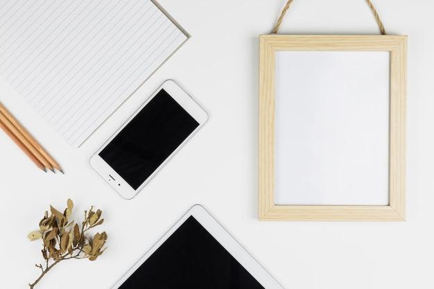 Tablet vicino a smartphone, carta, matite e cornice per foto