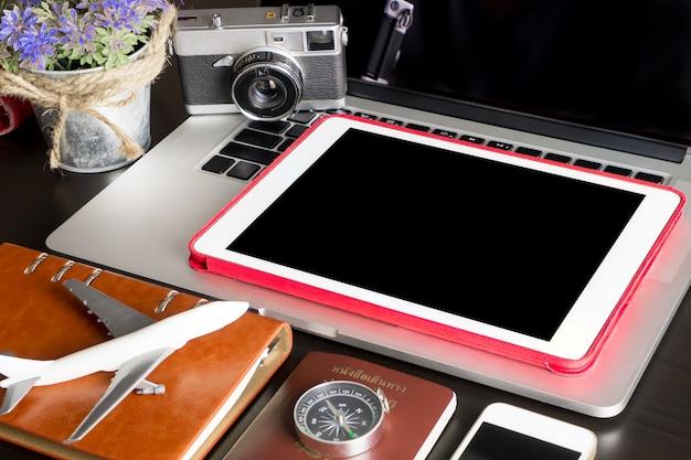 Tablet vuoto vuoto con oggetti di viaggio sul tavolo dell'ufficio