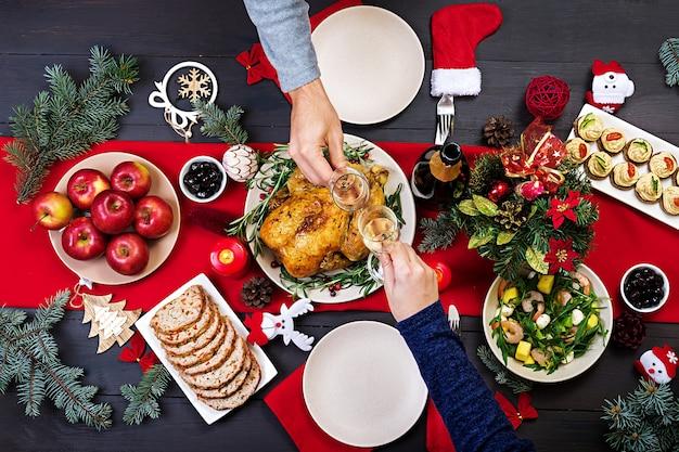 Tacchino al forno il tavolo di natale è servito con un tacchino, decorato con tinsel luminoso