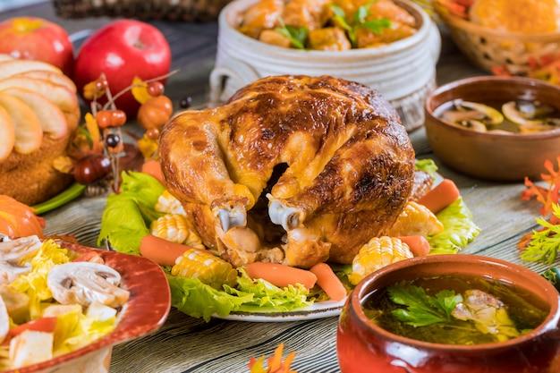 Tacchino arrosto guarnito con mais e molti piatti su un tavolo rustico.