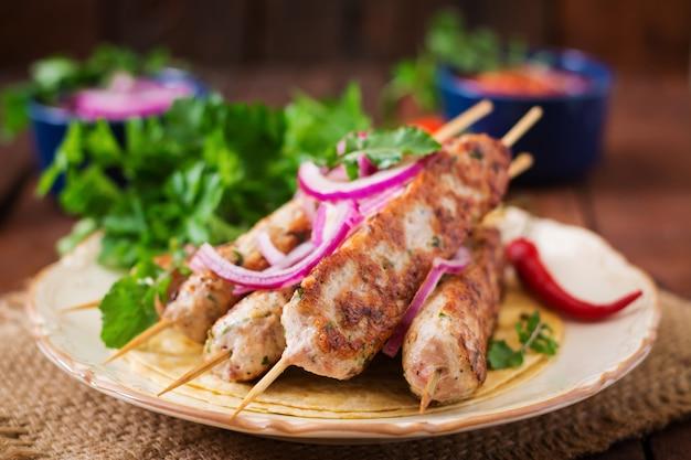 Tacchino grigliato di kebab macinato di lula (pollo) sul piatto.