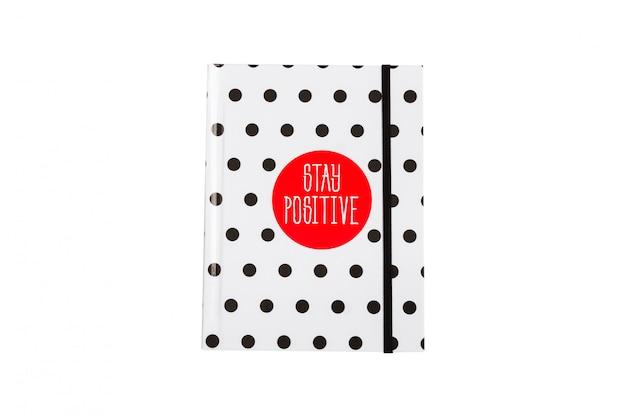 Taccuino a pois in bianco e nero con circla rossa e iscrizione positiva sulla copertina.