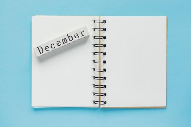 Taccuino a spirale pulito per note e messaggi e barra del calendario in legno di dicembre. posa piatta minima per affari
