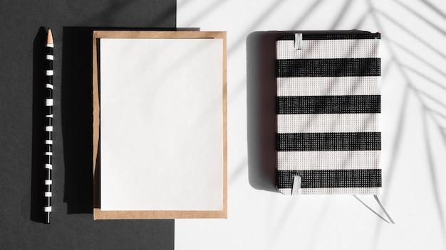 Taccuino a strisce in bianco e nero e coperta bianca con una matita a strisce in bianco e nero su uno sfondo in bianco e nero con un'ombra di foglia