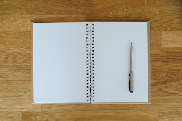 Taccuino aperto dello spazio in bianco con la penna d'argento sulla vista di legno del piano d'appoggio.