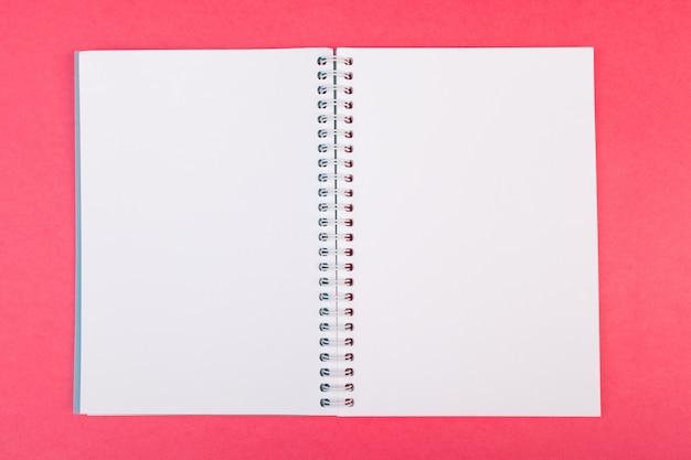 Taccuino aperto in bianco sulla vista superiore rosa luminosa