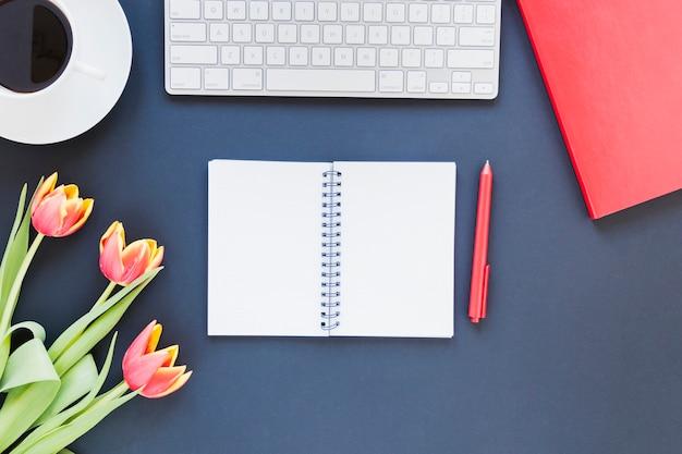 Taccuino aperto vicino alla tazza e alla tastiera di caffè sullo scrittorio con i fiori del tulipano