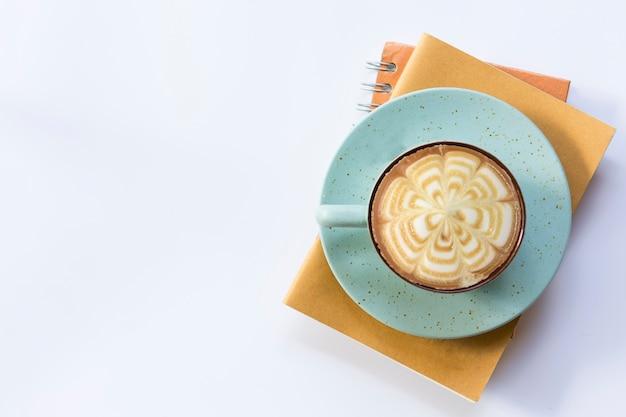 Taccuino arancio con caffè marrone del taccuino e della tazza su fondo isolato.
