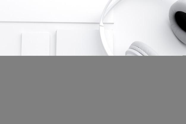Taccuino, auricolare e matita in bianco aperti di vista superiore sullo scrittorio bianco
