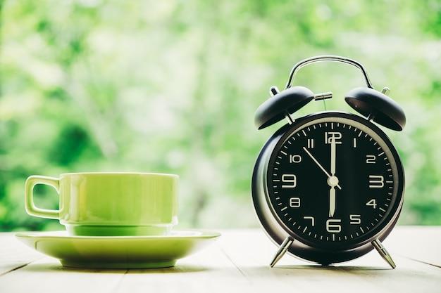 Taccuino bianco della tazza di caffè della tenuta della mano, penna, sveglia su fondo netural