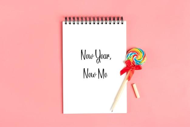 Taccuino bianco per appunti, penna - lecca-lecca su sfondo rosa