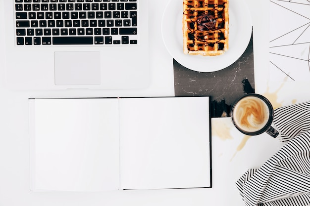 Taccuino bianco vuoto; il computer portatile; cialda; tazza di caffè e tovaglia su sfondo bianco