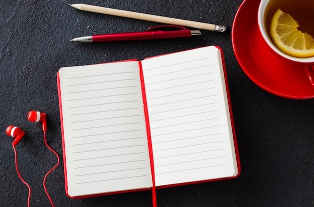 Taccuino, computer portatile, cuffie e tazza rossi in bianco di tè. concetto di business o di educazione.