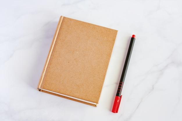 Taccuino con la penna su fondo di marmo bianco per il concetto dei rifornimenti di scuola e dell'ufficio