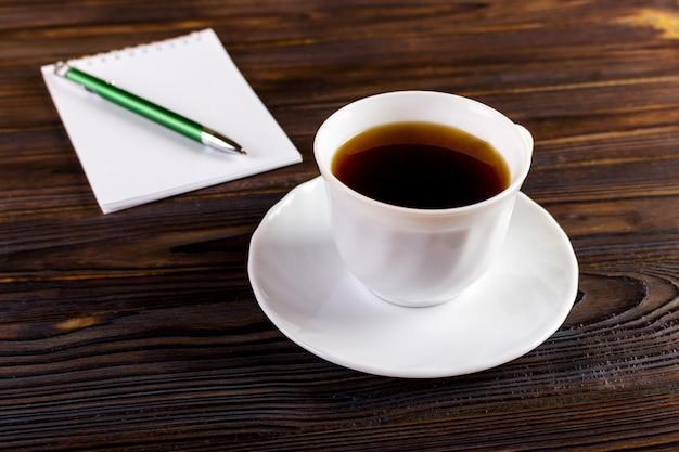 Taccuino con la tazza di caffè e della penna, concetto di affari