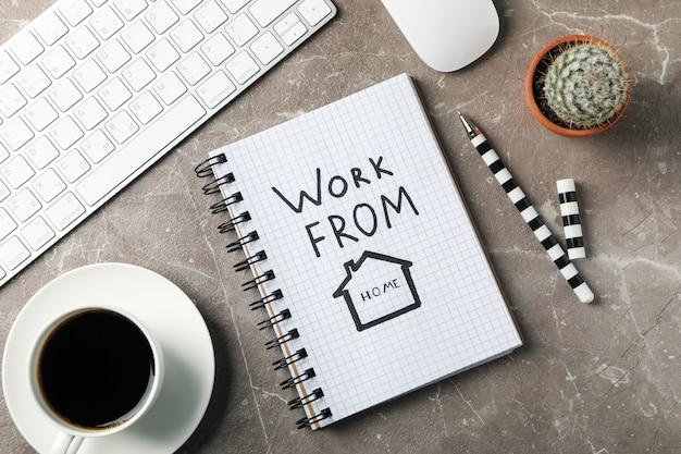 Taccuino con lavoro da casa su superficie marrone. posto di lavoro