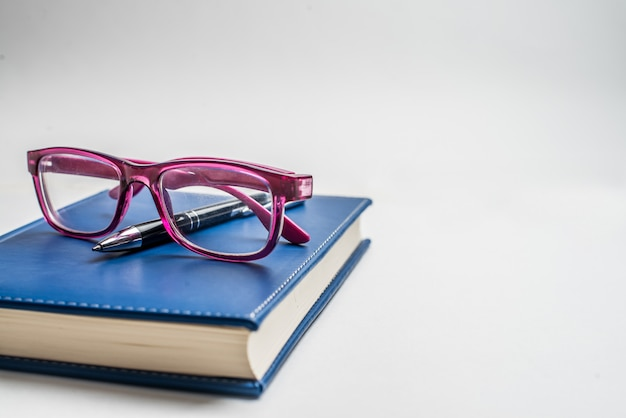Taccuino con occhiali e penna, libro con gli occhiali, taccuino blu con gli occhiali, libro con una tazza di tè
