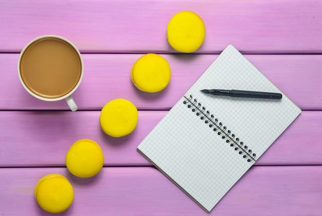 Taccuino con una penna, una tazza di caffè e amaretti gialli su un tavolo di legno viola. tendenza del minimalismo. vista dall'alto. disteso.