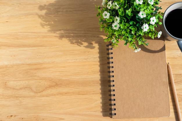 Taccuino con una tazza di caffè e una pianta sul tavolo di legno