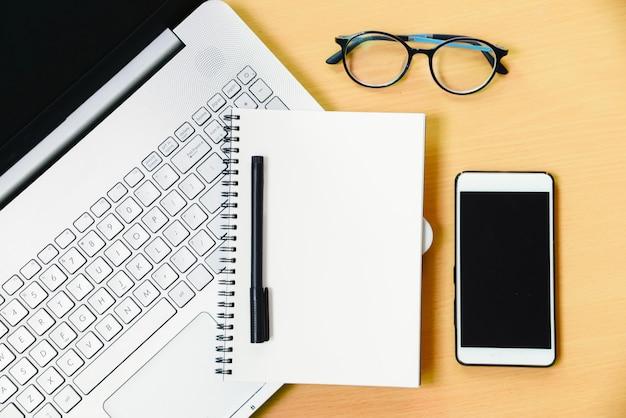 Taccuino del computer con il messaggio del taccuino dello smartphone e una penna sullo scrittorio funzionante in ufficio