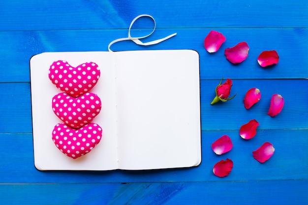 Taccuino del diario con i cuori del biglietto di s. valentino e della rosa su fondo di legno blu.