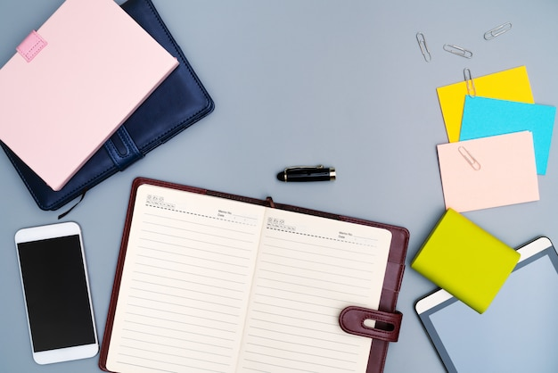 Taccuino del diario con lo smartphone, carta del bastone multicolore della cancelleria dell'ufficio
