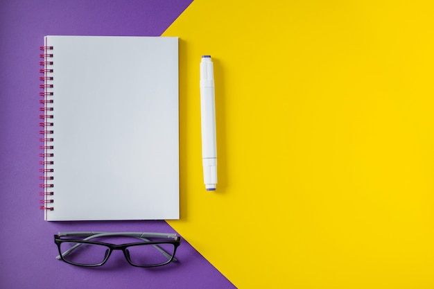 Taccuino della scuola sul blocco note a spirale giallo e porpora, su una tavola. sfondo vista dall'alto con copyspace. blocco note per ufficio disteso.