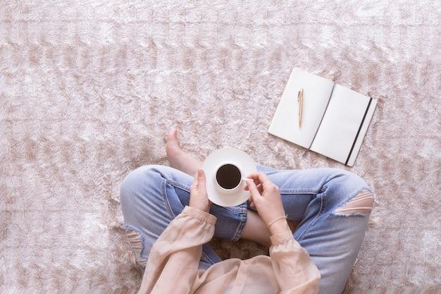 Taccuino della tenuta della donna alla scrittura delle note per il suo blog. blog e lavoro a casa concetto. copia spazio