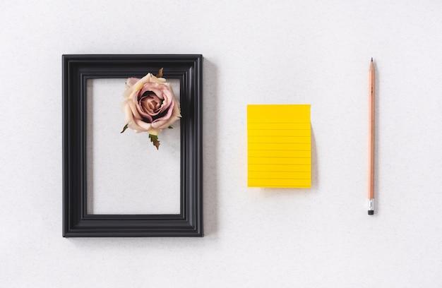 Taccuino dello spazio pastello e cornice nera con fiore rosa e matita