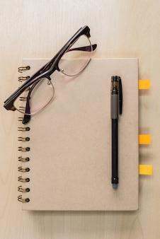 Taccuino di brown con gli occhiali e penna nera su fondo di legno