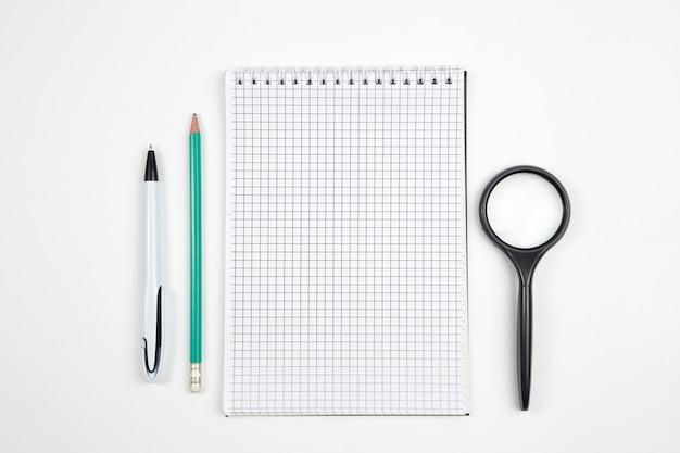 Taccuino di carta con la penna o la matita su fondo isolato bianco. vista dall'alto. disteso. modello