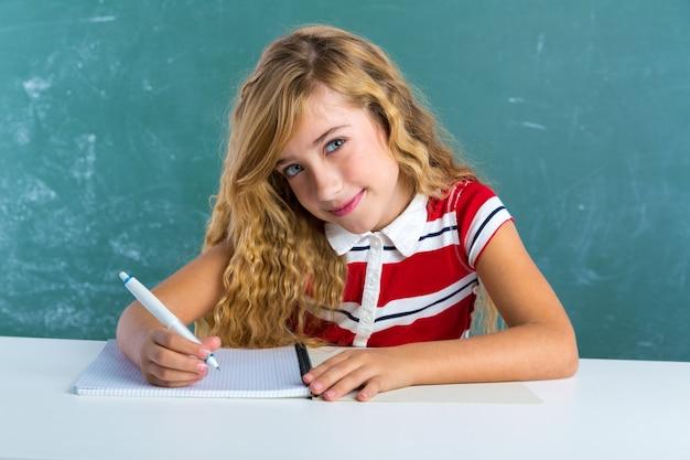 Taccuino di scrittura biondo della ragazza dello studente allo scrittorio della classe
